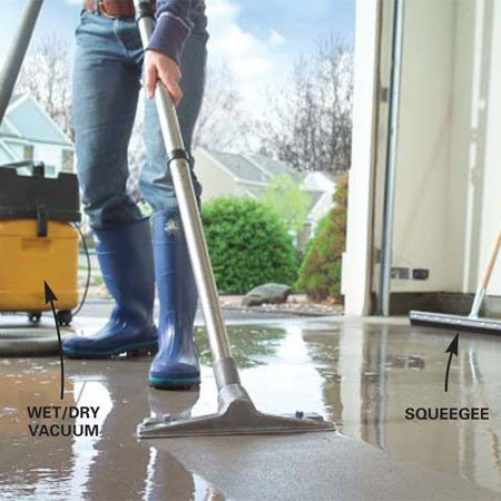 <b>Photo 3: Vacuum the wet floor</b></br> Push a rubber squeegee along the floor and pool the soap mixture into smaller areas. Vacuum up the solution for proper disposal.