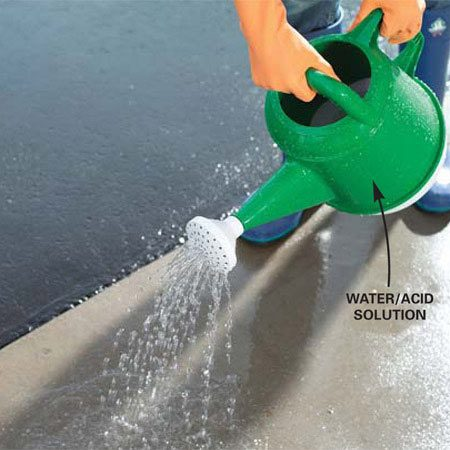 <b>Photo 4: Sprinkle the floor with acid/water solution</b></br> Pour 12 ozs. from a bottle of 32 percent muriatic acid (common formulation) into a gallon of water (1 part acid to 10 parts water) in a plastic sprinkler can, then sprinkle evenly over a 10 x 10-ft. area.
