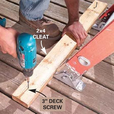 <b>Photo 2: Install a cleat</b></br> Screw a 2x4 cleat to the deck behind the ladder's feet to prevent the ladder from slipping backward.