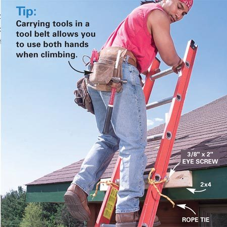 <b>Photo 4: Tie off the ladder top</b></br> Secure the top of your ladder by tying it to a solid anchor. Make a reusable anchoring rig by screwing two 3/8-in. x 2-in. eye screws into a 32-in. length of 2x4. Then screw the 2x4 to the fascia with 3-in. deck screws.