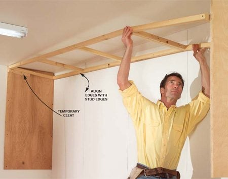 <b>Photo 6: Set the top ladder in place</b></br> Tack a temporary cleat 1-3/4 in. below the ceiling, rest the top ladder on it, and lift it into place. Screw it to the end panels and then fasten it to any available ceiling framing and to the wall with lag screws.