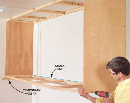 <b>Photo 7: Screw on the bottom ladder</b></br> Snap a chalk line 1-1/2 in. above the bottom of the end panels, add another temporary cleat and screw the bottom ladder to the end panels. Align the 2x2 rail to the chalk line and nail it to the wall studs.