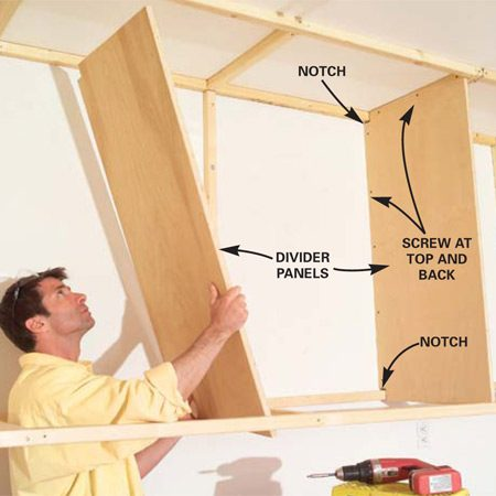 <b>Photo 10: Place the divider panels</b></br> Lift the divider panels into position. Using 2-in. screws, attach them to the wall cleats and top ladder rungs only