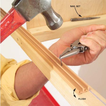 <b>Photo 12: Add the sliding door tracks</b></br> Cut the tracks to length, then tack the bottom track to the bottom rail with 1-in. brads. Punch the brads to the bottom of the grooves with a nail set. Spread polyurethane glue on the top track and tack it into place.