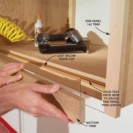 <b>Photo 17: Add trim</b></br> Cut 1x2 end panel trim to extend about 3/4 in. below the end panel. Nail into place. Cut and nail 1x3 trim for the top and bottom rails.