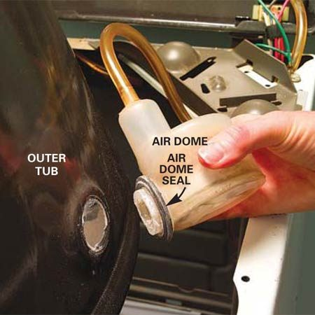 <b>Photo 8: Remove the air dome</b></br> Twist the air dome a quarter turn and pull it free from the outer tub. Pry off the old air dome seal and replace it with a new one.