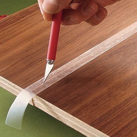 <b>Use tape to catch excess glue</b></br> To prevent stains caused by oozing glue along joints, clamp the pieces together without glue. Put tape on the joint, then cut along it with a sharp blade. Separate the pieces, apply the glue and clamp them together again. The glue will ooze onto the tape, not the wood. Peel off the tape before the glue dries.