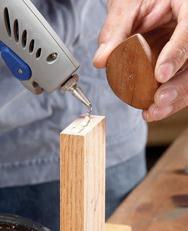 <b>Hot glue holds small stuff better than clamps</b></br> When you have to cut, shape, file, sand or finish something small, reach for your hot glue gun and glue the piece to a pedestal stick. The hot glue will hold just about anything as well as or better than any clamp ever could—if using a clamp is even possible. When your project is complete, try to pop it loose with a putty knife, but don't use too much force—you might tear out the wood or break the piece.
