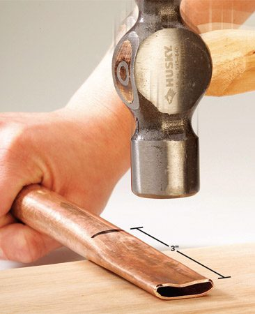 <b>Photo 3: Flatten the decorative ends</b></br> Form spear points on the ends of the tubes according to the plan. Start by flattening a 3-in. section of the end of the tubing against a scrap of hardwood lumber or other hard surface.