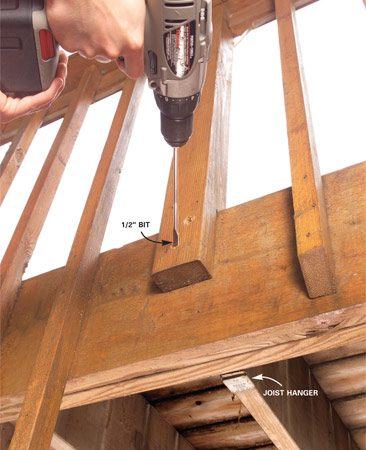 <b>Photo 1: Drill bolt holes</b></br> Drill two 1/2-in. holes through the post and framing. Offset the holes to prevent splitting the post. Angle the hole to avoid joist hangers.