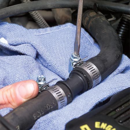 <b>Tighten the clamps</b></br> Make sure the hose is slipped onto the coupling and tighten both clamps. Don't cowboy the hoses; they may be fragile and in need of replacement. Add water to your reservoir or radiator, or drive (no longer than 10 minutes!) to the nearest place you can get coolant. This fix isn't permanent, so make an appointment to have your hoses and coolant checked.