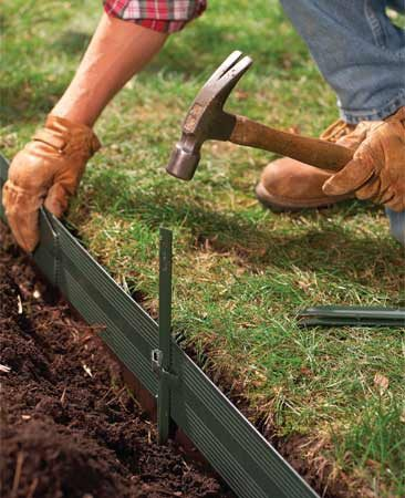 <b>Photo 3: Support the edging with stakes</b></br> Drive stakes to set the depth at about 1/2 in. above the soil level of the lawn. If the edging drops too low, pry it up with the tip of your shovel.