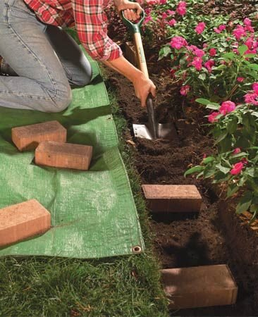 <b>Photo 2: Dig a wide trench</b></br> Dig a 4-in. deep trench about an inch wider than the brick pattern, using a square spade. Cut the edge along the grass smooth and square.