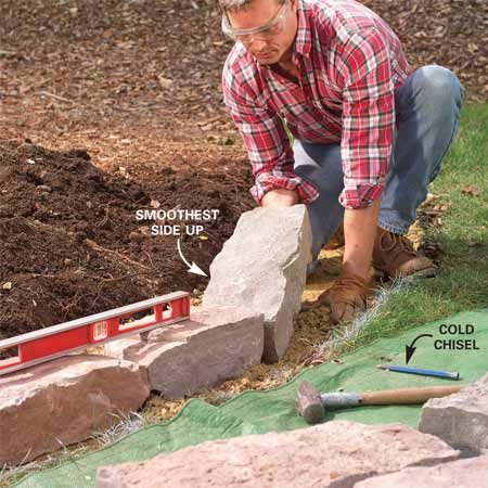 <b>Photo 3: Set the first row of stone</b></br> Lay the first row of stones about 4 in. back from the grass edge. Push in more gravel or dig it out to align and level them. Wear goggles when chipping stones.