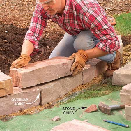 <b>Photo 4: Lay the second row</b></br> Stack the second row of stones onto the first, overlapping the joints. Test several stones to find the most stable fit.