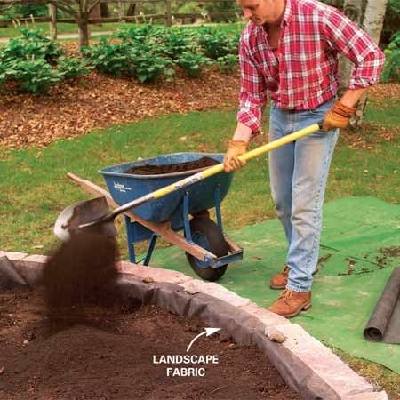 <b>Photo 5: Fill the raised bed with topsoil</b></br> Lay a strip of landscape fabric against the back of the stones and fill the planting bed with topsoil. Trim off excess fabric later.