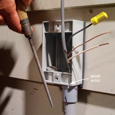 <b>Photo 5:   Bring the cable to the power source</b></br> Feed the cable through the conduit and screw the exterior extension box to the existing box. Fasten the conduit to the siding with a strap and file two 1/8-in. deep weep holes at the bottom of the box.