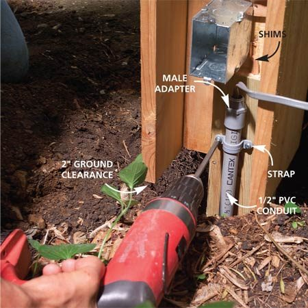 <b>Photo 8: Set the post</b></br> Set the post assembly in the hole and adjust the height, then fill and pack soil around the post bottom. Assemble and glue the plastic conduit parts, run the cable through it and strap it to the post.