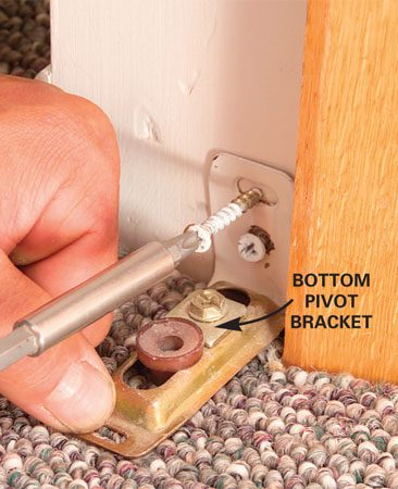 <b>Photo 2: Adjust the bottom bracket</b></br> Tighten a loose bottom bracket with 1-1/2 in. screws driven through the drywall into the framing. Avoid screwing through the carpeting if possible.