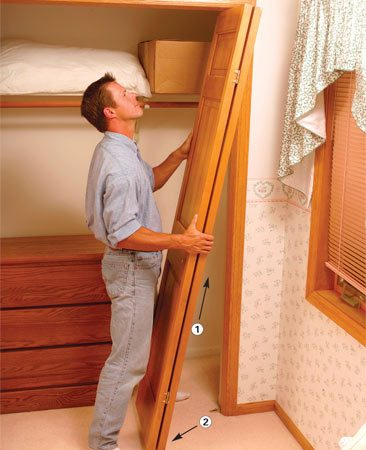 <b>Photo 2: Remove the door</b></br> Open the door completely and lift it to compress the top pivot spring (1). Swing the door bottom out from the bottom bracket (2). Pull the door down and out of the top pivot bracket.