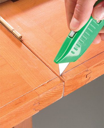 <b>Photo 3: Score the cutting line</b></br> Mark the cutting line on the backside of the door and then score the line with a utility knife to reduce splintering.