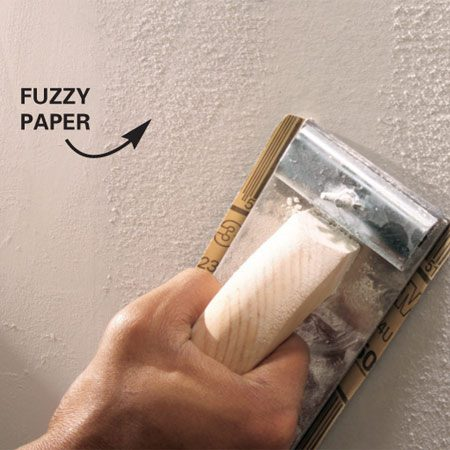 <b>Sand the wall after priming</b></br> Prime the walls and sand them lightly after the primer dries to remove paper fuzz and lumps.