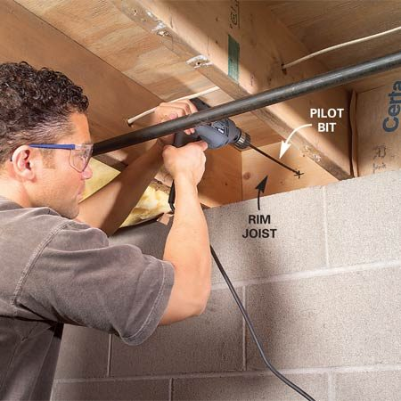 <b>Photo 2: Drill a test hole in the rim joist</b></br> Mark the center of the rim joist and drill a test hole with a 1/4-in. bit. Locate the hole outside and check for obstructions.