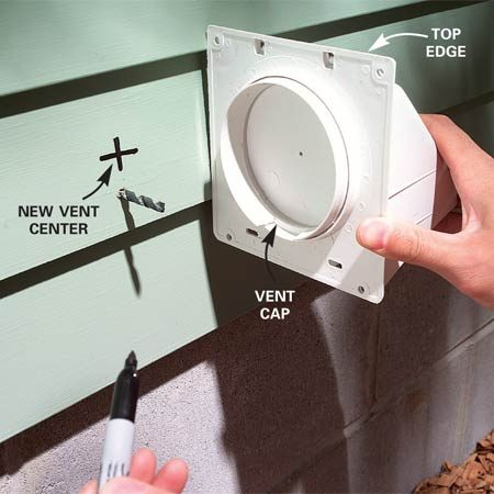 <b>Photo 3: Adjust the hole to fit the siding</b></br> Shift the hole so the top of the vent cap rests on the high point of the lap siding. Pull the vent cap and duct apart to make measuring easier.
