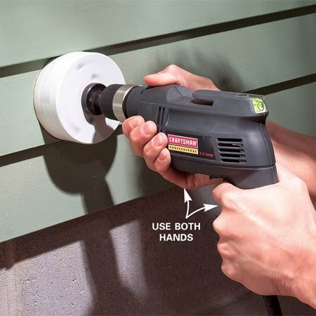 <b>Photo 4: Drill the vent hole in the siding. </b></br> Bore a 4-1/4 in. hole with a hole saw. Hold the drill level and steady. Pull the drill back frequently to clear the sawdust and let the drill motor cool.