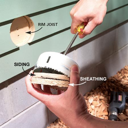 <b>Photo 5: Drill through the rim joist</b></br> Stop and pry out siding and sheathing from the saw as you go. Then continue your cut through the rim joist.