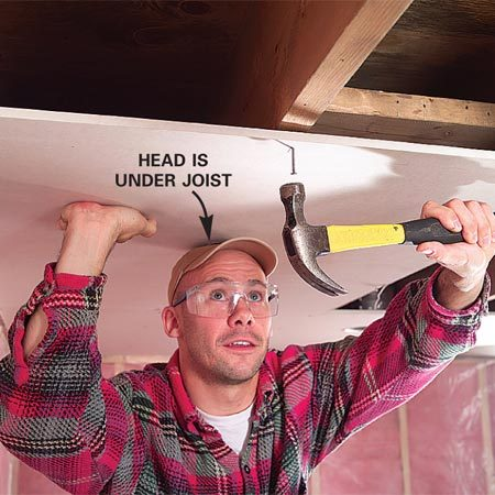 <b>Photo 6: Set nails before you lift</b></br> With a few nails already in place, you won't need a third hand to hang ceiling rock. Use your head to support the sheet, too.