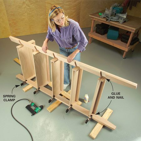 <b>Photo 8: Nail the shelves in place</b></br> Clamp the shelves into one upright. Spread glue in the shelf notches of the other upright, position it flush with the front of the shelves and nail. Flip the unit over and attach the other upright.