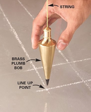 <b>Align the plumb bob</b></br> Ask a helper to steady the plumb bob and tell you which way to move the string to center it over the point on the floor.