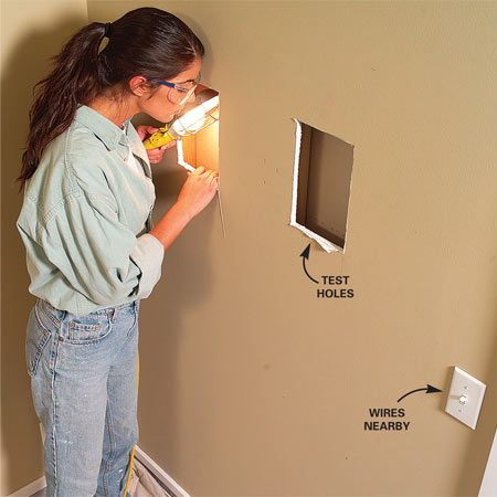<b>Photo 1: Check for mechanicals</b></br> Find nearby studs with a stud finder, then cut a small opening with a utility knife in each stud cavity and check for obstructions. Save the cutouts in case you have to repair the wall.
