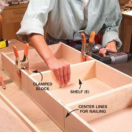 <b>Photo 6: Nail the shelves</b></br> Cut and nail the shelves into the deep box. Clamp square blocks to the sides to hold the shelf at a right angle while you nail it.