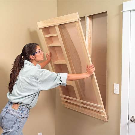 <b>Photo 10: Place the message center in wall</b></br> Set the completed message center in the opening and level it. Then nail through the trim into the studs to secure it.