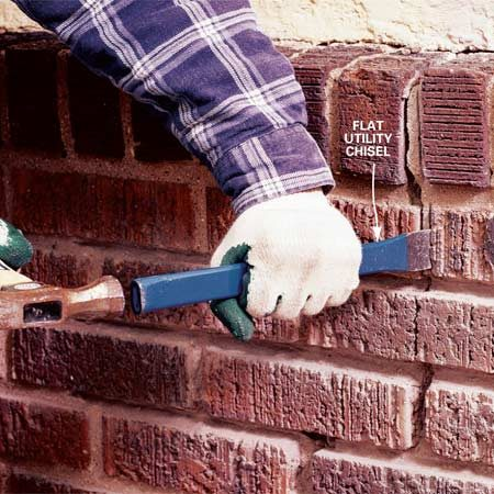 <b>Photo 2: Chip out loose mortar</b></br> Position a flat utility chisel at the edge of the brick and drive it toward the relief cut to fracture and remove the mortar.