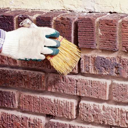<b>Photo 3: Clean the joints</b></br> Clean out all the loose dust from the brick cavity using a whisk broom or compressed air. Moisten the cleaned cavity with a garden hose.