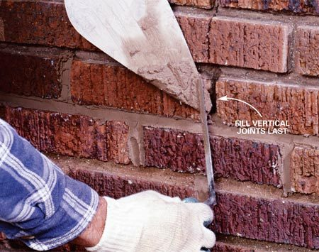 <b>Photo 6: Fill the vertical joints last</b></br> Load smaller amounts of mortar onto the back of the brick trowel, hold the trowel tip along the vertical joints and above the horizontal joints—tight to the brick—then sweep and pack the mortar into the cavity using the pointing trowel.