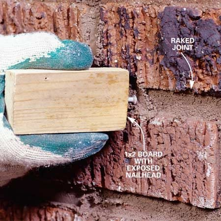 "<b>Photo 7: Rake the joints </b></br> Drive a 6d box nail into a short 1x2 board so that it matches the depth of the existing joints. To ""rake"" joints, hold the board perpendicular to the bricks and move it back and forth, first along the vertical joints and then the horizontal joints. Other joint profiles require other shaping tools."