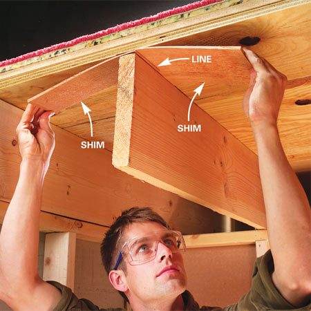 <b>Photo 1: Shim between the joist and subfloor</b></br> Slide a pair of shims into the gap for a snug fit. Draw a line on each shim to mark the depth. Don't wedge the gap wider.