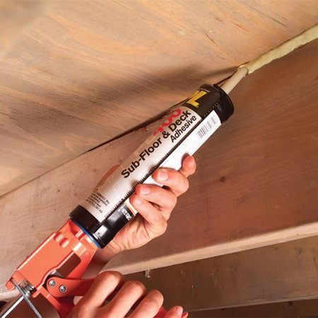 <b>Force adhesive into the gaps</b><br/>Squeeze a thick bead of construction adhesive into the crack along both sides of the squeaky joist and subfloor. Apply adhesive to adjacent joist/ subfloor joints as well.