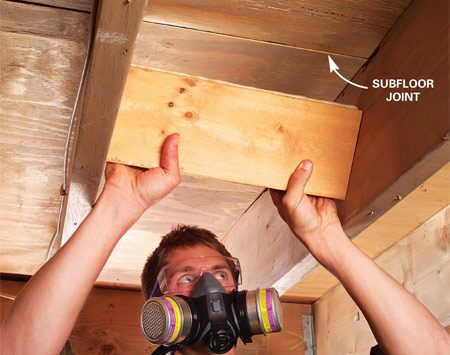 <b>Photo 1: Insert the block</b></br> Cut 2x8 blocking to fit snugly between joists. Add construction adhesive to the top and slide it into place.