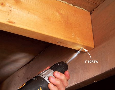 <b>Photo 2: Screw the block</b></br> Predrill angled pilot holes with a 1/8-in. bit. Drive 3-in. wood screws to force the block snug against the subfloor seam. Drive an additional pair of screws (or 16d nails) through the joist into the block on each end.