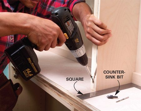 <b>Photo 9: Screw the shelf units to the cabinet</b></br> Position the shelves, then fasten the fronts of the shelf units with 2-1/2 in. screws. Drill a recess for the screwhead with a countersink bit and then drill a pilot hole.
