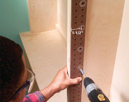 <b>Photo 12: Use pegboard as a guide for drilling holes</b></br> Drill holes for the adjustable shelf supports (usually 1/4 in.) using pegboard as a guide. To minimize splintering, use a brad point bit. Mark the hole depth with masking tape.