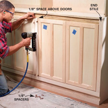<b>Photo 15: Install the stiles</b></br> Position stiles using 1/8-in. spacers. Stiles between doors should stand exactly 1/8 in. higher than the doors. Run end stiles up to the cabinet top. Scribe and trim the wall stile if the wall is uneven.