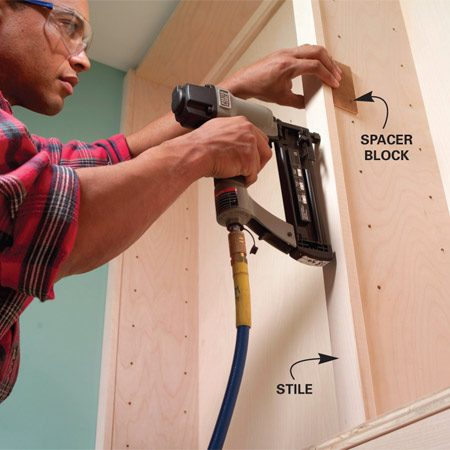 <b>Photo 17: Nail the shelf stiles in place</b></br> Center the shelf stiles using thin spacer blocks and fasten with 2-in. brads. Aim carefully so brads don't poke through the sides of the shelf unit.