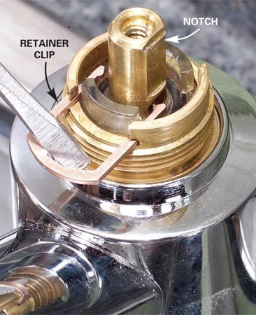<b>Step 4: Remove the retainer clip</b></br> Photo 4: Pry out the brass retainer clip with the tip of a screwdriver. Grab the clip with pliers and pull it the rest of the way out to avoid losing it.