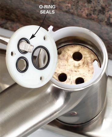 <b>Step 4: Replace the o-ring seals</b></br> Photo 4: Lift out the plastic disc (on some faucets) and replace the O-rings under it. Inspect the holes in the faucet body and clean them out if they're clogged.